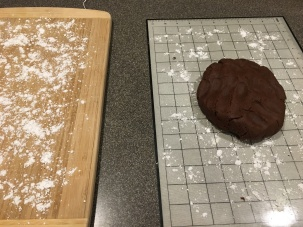 Chocolate dough, ready to be rolled out on mat with powdered sugar.